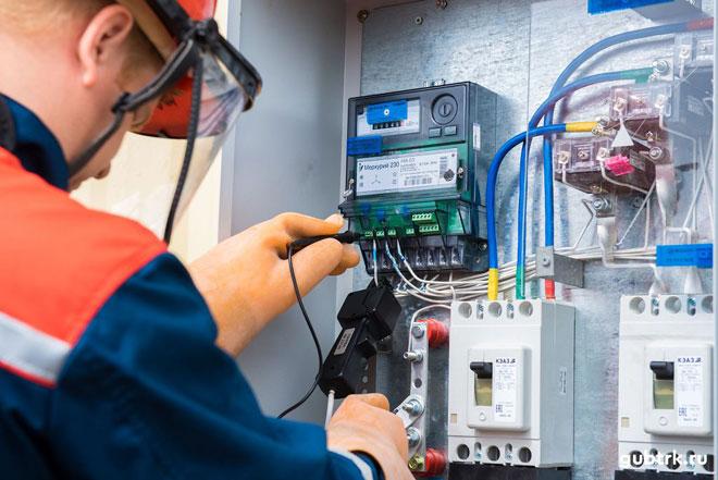 Электрик проверяет работоспособность электросчётчика.