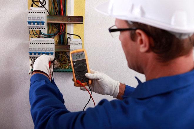 Электрик производит замер напряжения мультиметром.