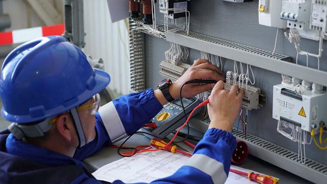 Инженер-электрик проверяет и налаживает электросхему.